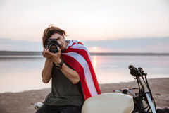 Man making photo with camera while sitting on his motocycle Stock Image