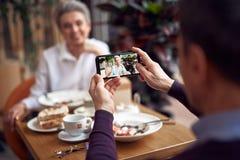 Man making photo of elegant lady on mobile phone. Enjoyable meetings. Close up portrait of men making photo of smiling elegant aged women on mobile phone while stock photo