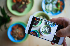 Man making photo of his lunch on smartphone. Delicious and nourishing dinner Stock Image