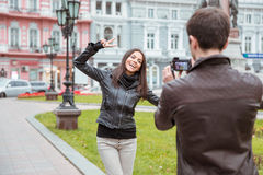 Man making photo of laughing woman outdoors Stock Images