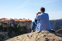 Man making photo near The Holy Monastery of Varlaam on the cliff at Meteora rocks, Greece Royalty Free Stock Photos