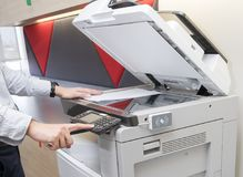 Man making photocopy of document on a copy machine with access control for key card. Man is making photocopy of document on a photocopier with access control royalty free stock image