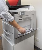Man making photocopy of document on a photocopier machine with access control for key card. Man is making photocopy of document on a photocopier with full royalty free stock image