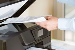 Man making a photocopy. Performing a photocopy clerk with multifunction printer Stock Photography
