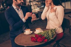 A man making proposal in a cafe. A men making proposal in a cafe. Cropped close up photo of lovely cute rich successful guy asking girlfriend`s hand and heart royalty free stock image