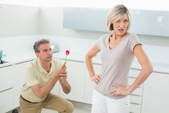 Man making a proposal to woman in kitchen Royalty Free Stock Photos