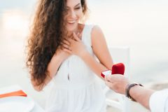 Man making propose with ring to excited girlfriend. In romantic date stock photo
