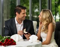 Man making propose to his girlfriend. Man holding box with ring making propose to his girlfriend stock photography