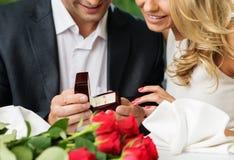 Man making propose to his girlfriend. Man holding box with ring making propose to his girlfriend stock photos
