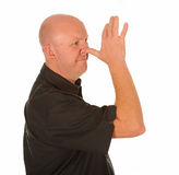 Man making rude gesture. Side view of bald man with thumb on nose making rude or insulting gesture, white background Royalty Free Stock Image