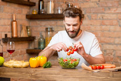 Man making salad. Handsome bearded man in white t-shirt making salad with tomatoes and pepper in the kitchen. Healthy and vegan food concept Royalty Free Stock Image