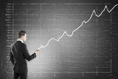 Man making sales graph on blackboard. Man drawing graph on large blackboard. Concept of successful business strategy and income growth in corporation Royalty Free Stock Photography