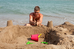 Man is making sandcastle on the beach Royalty Free Stock Images