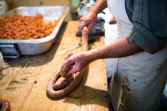 Man making sausages the traditional way using sausage filler. Royalty Free Stock Photography