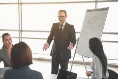 Man making schematic analysis to partners. Young manager in suit reaching out to the audience in front of him while standing close to whiteboard with chart on it Royalty Free Stock Photo