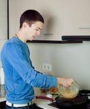 Man making scrambled eggs Stock Images
