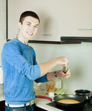 Man making scrambled eggs in frying pan Stock Image