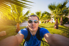 Man is making selfie in the palm garden Royalty Free Stock Photo