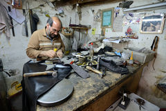 Man making shoes in a market royalty free stock photos