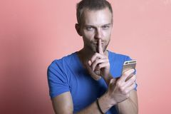 Man making the silence finger with mobile phone in hand.  royalty free stock images
