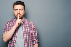Man making silence gesture on gray background. Serious man with silence symbol, studio portrait stock images