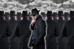 Man making a silence gesture. Mysterious man making a silence gesture while standing out from the crowd stock photo