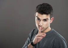 Man making a silence gesture. Studio portrait of a young man making a silence gesture, gray background Stock Image