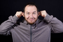 Man making silly face by pulling his ears. Man pulling his ears isolated on black background Stock Images