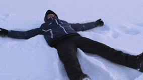 Man is making snow angel in deep snow, having fun in winter