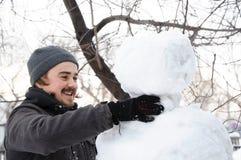 Man making snowman Royalty Free Stock Photography