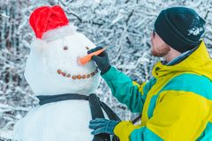 Man making snowman outdoors at frosty winter park. Concept royalty free stock image
