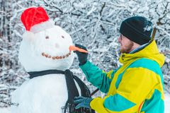 Man making snowman outdoors at frosty winter park. Concept royalty free stock photo