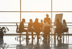Man making startup analysis to colleagues. Group of people sitting at the office table while their partner standing near board with chart. Panoramic window on Stock Images