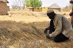 Man making straw wall for african houses, roof Royalty Free Stock Photos