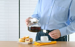 Man making tea. For breakfast with donuts Stock Image