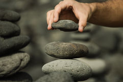 Man making a tower with stones. On the beach Royalty Free Stock Photo