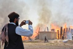 A man making video of fire in wood stalls. stock photos