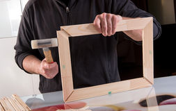 Man making wooden frame. Incognito man master in black sweater with mallet making wooden frame from workpieces Royalty Free Stock Photo