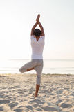 Man making yoga exercises outdoors from back Royalty Free Stock Photo