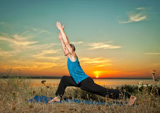 Man making yoga exercises outdoors Stock Photography