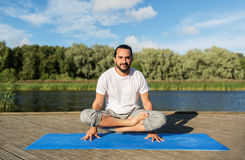 Man making yoga in scale pose outdoors Stock Photos