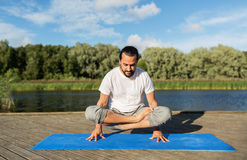Man making yoga in scale pose outdoors Royalty Free Stock Image