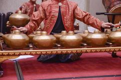 Man with Malay songket costume playing traditional music instrum. Ent called Gamelan. selective focus shot Royalty Free Stock Photography