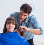 Man male hairdresser doing haircut for woman royalty free stock photo