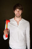 Man With Mallet. Smiling young man holds up a red and yellow mallet Royalty Free Stock Photo