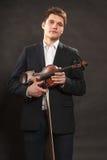 Man man dressed elegantly holding violin Royalty Free Stock Photo