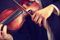 Man man dressed elegantly playing violin Stock Photos