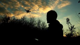 Man manages drone. Silhouette on background of the sunset sky stock footage