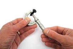 Man& x27; mani di s vedute facendo uso di un micrometro imperiale d'annata per misurare Fotografia Stock Libera da Diritti
