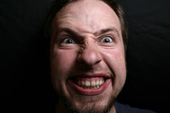 Man with maniacal grin. At the viewer Royalty Free Stock Photos